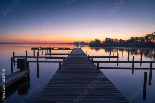 Acrylglas Pier Man on a jetty enjoying a tranquil dawn at the Leekstermeer, Holland.