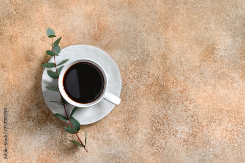 Cup of black coffee on a beige textured table with a branch of eucalyptus. Top view, copy space, minimalism style.