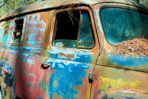obraz lub plakat Old vintage rustic car sitting in a junk yard.