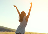 Fototapeta Natura - Happy girl with arms raised in sunshine  © kegfire