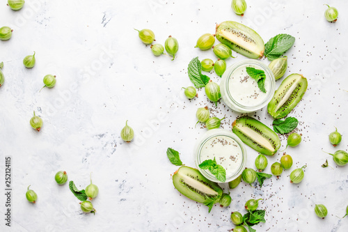 Smoothies and milkshakes from gooseberry, milk cocktail with kiwi and yogurt? chia seeds, gray kitchen table background, flat lay, top view - 252124115