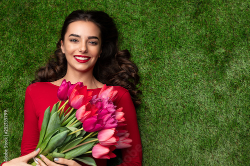 Adorable woman with flowers lying on meadow