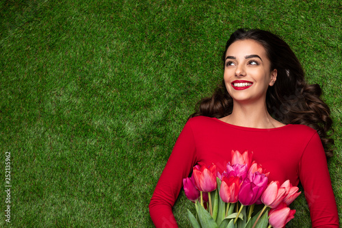 Young dreaming girl with flowers lying on meadow