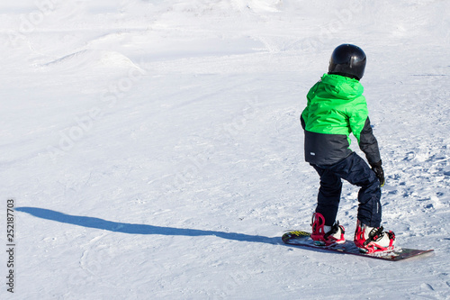 obraz lub plakat Kid on snowboard in winter sunset nature. Sport photo with edit space