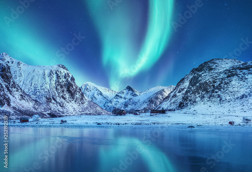 Aurora borealis on the Lofoten islands, Norway. Green northern lights above mountains. Night sky with polar lights. Night winter landscape with aurora and reflection on the water surface. Norway-image © Biletskiy Evgeniy