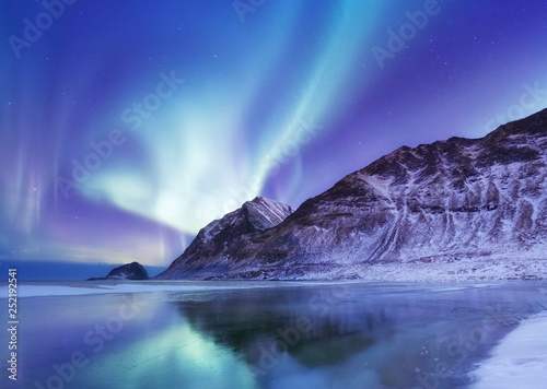 Aurora borealis on the Lofoten islands, Norway. Green northern lights above mountains. Night winter landscape with aurora and reflection on the water surface. Norway-image © Biletskiy Evgeniy