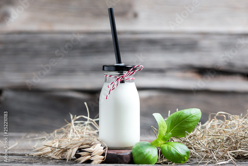 Fresh milk in glasses in front of a rustic vintage background © Hetizia