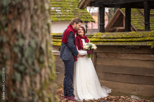 Beautiful wedding couple posing near old houses in village © hreniuca