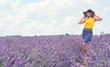 Girl in hat in lavender flowers field.