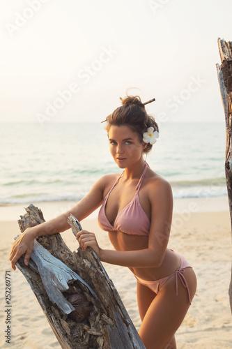 Leinwanddruck Bild Sexy woman is posing beside the driftwood on the beach