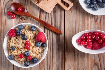 Top view of porridge with blueberries and raspberries on wooden background. Vegan breakfast.