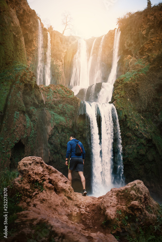 Young man sitting on a stone against Ouzoud waterfalls - Morocco, Africa. Concept of travel.  © tibor13