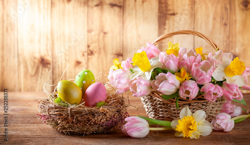 Easter holiday basket with beautiful spring flowers and nest with Easter eggs. - 252288371