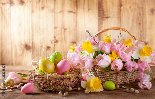 Easter holiday basket with beautiful spring flowers and nest with Easter eggs. - 252288375