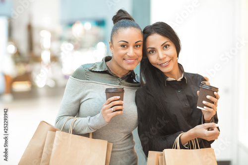 Two African American female friends having coffee and shopping together