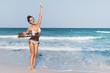 Leinwandbild Motiv Sexy woman wearing swimsuit with old wooden sign on the beach