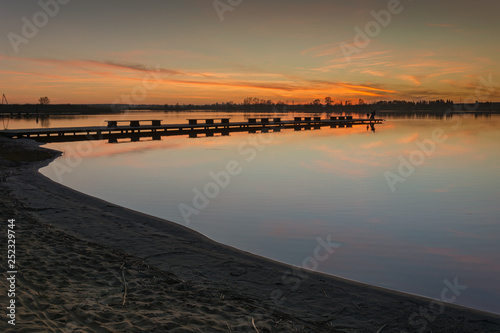 Acrylglas Pier Sandy shore of a calm lake, jetty and clouds after sunset
