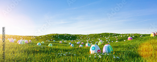 Many colorful easter eggs painted with water paint in the grass of a meadow for easter - 252359991