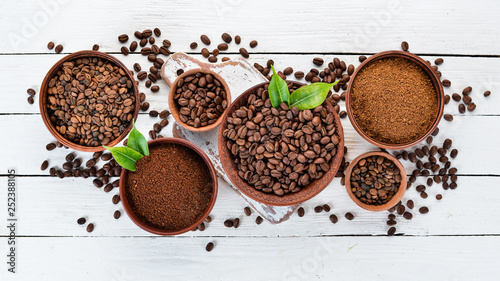 Ground coffee and coffee beans. On a white wooden background. Top view. Free space for your text. - 252388105