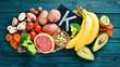 Leinwandbild Motiv Foods containing natural potassium. K: Potatoes, mushrooms, banana, tomatoes, nuts, beans, broccoli, avocados. Top view. On a blue wooden background.