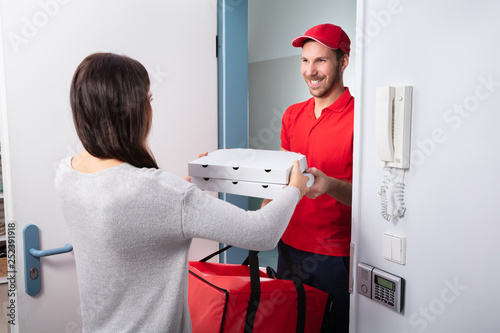 Man Delivering Pizza To Woman - 252391918