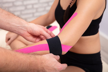 Man Applying Black Physio Tape On Woman's Hand © Andrey Popov