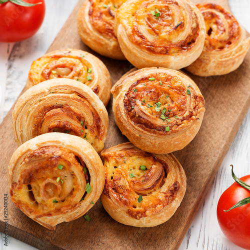Rolls of puff pastry with bacon and cheese .
