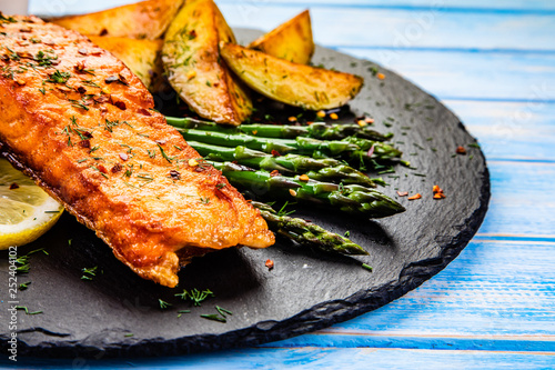 Grilled salmon with baked potatoes, asparagus and vegetable salad - 252404102