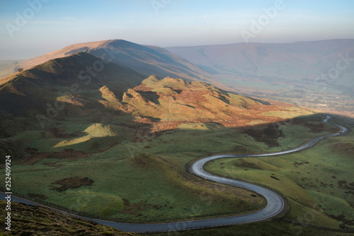 A scenic road winds its way through the Edale Valley on a foggy Winter sunrise in the Peak District in England