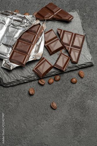 dark chocolate bar and pieces on dark concrete background