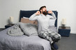 Leinwandbild Motiv Problem with early morning awakening. Get up early. Tips for waking up early. Man bearded hipster sleepy face pajamas waking up bedroom interior. Daily schedule for healthy lifestyle. Rest and relax