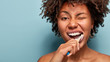 Leinwanddruck Bild - Tooth care concept. Slim naked young woman blinks eye, has daily routine after shower, brushes teeth with tootbrush, has healthy skin, isolated over blue background, free space for your promotion.