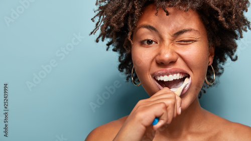 Leinwanddruck Bild Tooth care concept. Slim naked young woman blinks eye, has daily routine after shower, brushes teeth with tootbrush, has healthy skin, isolated over blue background, free space for your promotion.