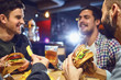 Happy friends eat burgers, drink beer in a bar.