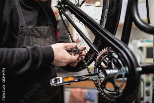 Leinwandbild Motiv Bicycle mechanic in a workshop in the repair process.