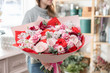 beautiful fresh cut bouquet of mixed flowers in woman hand. the work of the florist at a flower shop. Red and pink color