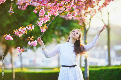 Leinwandbild Motiv Woman enjoying cherry blossom season in Paris, France