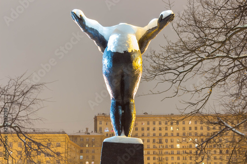 Monument to girl bather back view. Snow on the monument, winter evening in the park. © PhotoBank