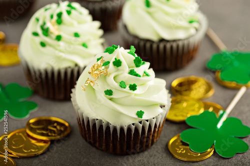 Saint Patrick day chocolate mint cupcakes with green frosting and golden leaf - 252541596