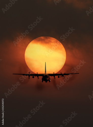 obraz PCV Portrait of transport aircraft in front of big sun in background