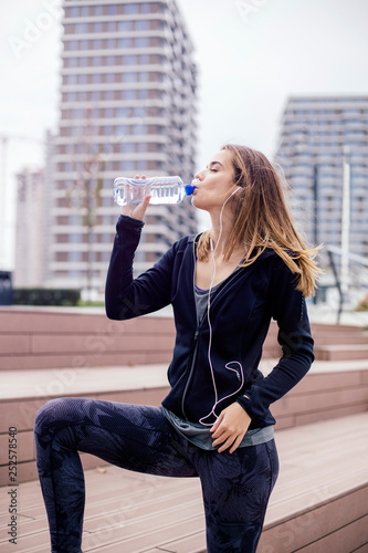 Young woman is refreshed after the training - 252578540