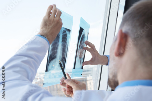 obraz lub plakat Group of doctors discuss x-ray