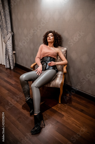 Sexy model with a curly hair, shooting in the interior, bright girl, fashion model
