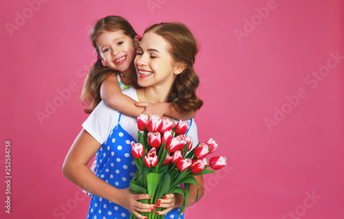 happy mother's day! child daughter   gives mother a bouquet of flowers on color pink background. - 252584758