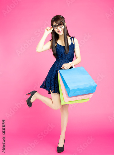 young women holding shopping bags on pink background - 252585799