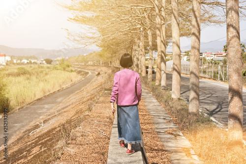 Asian woman walk under the tree