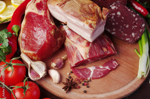 Smoked meat and ham with vegetables on the kitchen board - 252592936