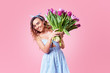 Young happy smiling redhead woman holding bouquet of colorful spring flowers isolated on pink background. Pink tulips, festive bouquet in honor of women's day on March 8 or birthday