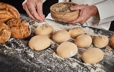 Baker sprinkling crushed grain and seeds on bun
