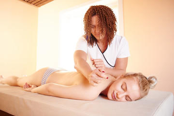 Beautiful authentic female masseur doing professional therapeutic massage to a young woman. Spa treatments, back therapy © amixstudio